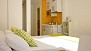 Seville Apartment - The double-bed with kitchenette beyond. There is a fitted-in wardrobe next to the bed.