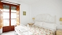 Seville Apartment - Bright bedroom with double bed and a large window.
