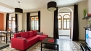 Seville Apartment - The living room has traditional floor tiles and stained glass windows.