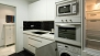 Sevilla Apartamento - The kitchen also includes a washing machine and an oven.